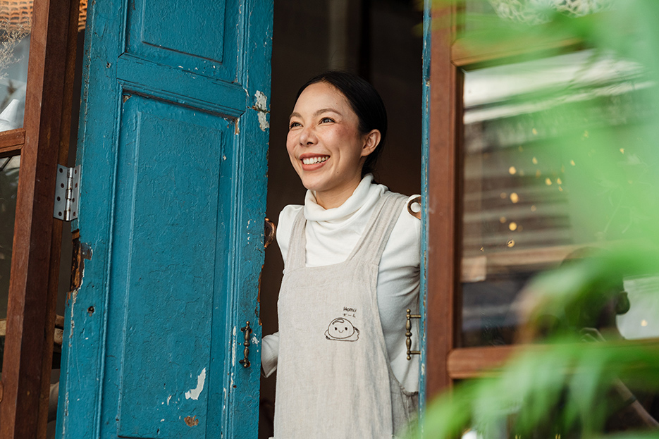 Happy ethnic woman in apron standing at entrance of own cafe